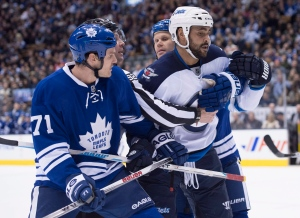 Winnipeg Jets' Dustin Byfuglien, right, scrums with Toronto Maple Leafs' David Clarkson, left, and Olli Jokinen, second from right, during first period NHL hockey action in Toronto on Saturday, Feb. 21, 2015. (Darren Calabrese / THE CANADIAN PRESS)