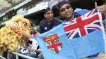 Rugby fans hold a Fiji national flag during the Rugby World Cup Sevens in Hong Kong on March 18, 2005. The country has launched a new campaign to design a new flag. (AP / Water Chan)