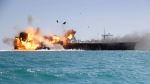 A replica of a U.S. aircraft carrier is exploded by Revolutionary Guard speedboats in the Persian Gulf, Iran. (AP / Tasnim News)