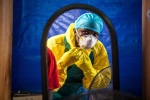 In this Thursday, Oct. 16, 2014 file photo, a healthcare worker dons in protective gear before entering an Ebola treatment center in the west of Freetown, Sierra Leone. (AP/Michael Duff, File)
