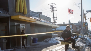 Two members of the Toronto Police Forensics unit step out of a McDonald's restaurant in the city's east end on Saturday, Feb. 28, 2015. (Chris Young / THE CANADIAN PRESS)