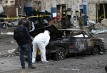 Lebanese police inspectors investigate the site of a deadly car bomb that exploded near a gas station in Hermel, about 15 kilometres from the Syrian border in northeast Lebanon in this Feb. 2, 2014 file photo. (AP / Hussein Malla)