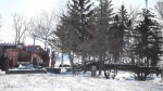 Firefighters looks on as the remnants of a house smolder following a fatal house fire in Kane, Man., on Feb. 25, 2015. (Trevor Hagan / THE CANADIAN PRESS)