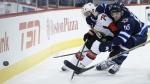 Winnipeg Jets' Mark Scheifele and Ottawa Senators' Mark Borowiecki fight for possession behind the Sens' net during second period NHL action in Winnipeg on March 4, 2015. (John Woods / THE CANADIAN PRESS)