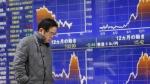 A man walks past an electronic stock indicator in Tokyo on March 3, 2015. (AP / Shizuo Kambayashi)