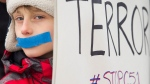 A young boy demonstrates to protest on a National Day of Action against Bill C-51, the government's proposed anti-terrorism legislation, in Montreal, Saturday, March 14, 2015. (Graham Hughes / THE CANADIAN PRESS)
