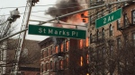Orange flames and black smoke billowed from the facade and roof of an apartment building near New York University collapsed on Thursday in a seven-alarm fire that hurt at least 12 people, three critically.<br><br>New York City firefighters work the scene of a large fire and a partial building collapse in the East Village neighborhood of New York on Thursday, March 26, 2015. (AP / Suzanne Mitchell)