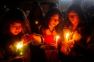Young women attend a candlelight vigil to observe Earth Hour in La Paz, Bolivia on March 29, 2014. (AP / Juan Karita)