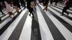 In this Jan. 14, 2015 file photo, people walk on a pedestrian crossing in Tokyo. (AP / Shizuo Kambayashi, File)