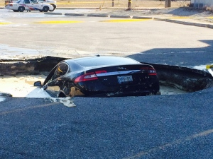 A Jaguar got stuck in a sinkhole that formed in a west-end Toronto parking lot on Wednesday, April 1, 2015. (Keith Hanley / CTV Toronto)