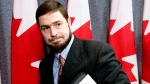 Maher Arar leaves a news conference with a copy of Justice O'Connor's report on the Arar inquiry after discussing the government's apology and compensation package at a news conference in Ottawa, Friday Jan. 26, 2007. (Tom Hanson / THE CANADIAN PRESS)