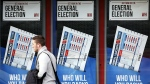 A member of the public walks past a betting shop window with a display for the General Election in Govan, Scotland on May 6, 2015. Britain goes to the polls in a General Election Thursday. (AP / Scott Heppell)