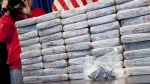 A firearm and 70 kilograms of heroin worth at least $50 million are displayed at a Drug Enforcement Administration news conference in New York on May 19, 2015. (AP / Mark Lennihan)