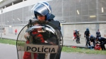 A riot policeman holds a crying boy as his father is attacked by other policemen with batons, right, outside of a stadium, in Guimaraes, Portugal. Portuguese prosecutors are investigating a policeman who beat a man in front of his young children and punched their grandfather on May 17, 2015. (AP / Delfim Machado)