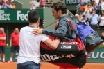 A boy who climbed down from the stands takes a selfie with Switzerland's Roger Federer in the first round match of the French Open tennis tournament against Colombia's Alejandro Falla at the Roland Garros stadium, in Paris on Sunday, May 24, 2015. (AP / David Vincent)