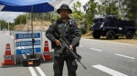 A Malaysian police officer stands guard at an outpost before the entry point to the Malaysia-Thailand border in Wang Kelian, Malaysia on Monday, May 25, 2015. (AP / Joshua Paul)