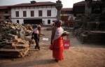 Nepalese people walk across the damaged temple area one month after the deadly 7.8 magnitude earthquake in Kathmandu, Nepal, Monday, May 25, 2015. (AP Photo/Niranjan Shrestha)