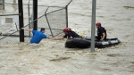 Rescue personnel grab the the hand of a man stranded in rushing water at the northwest corner of Lamar Blvd. and 15th St. in Austin, Texas on May 25, 2015. (AP / Austin American Statesman, Alberto Martinez)