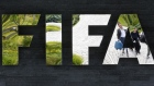 Two persons are reflected in the FIFA logo at the FIFA headquarters in Zurich, Switzerland, Wednesday, May 27, 2015. (AP / Michael Probst)