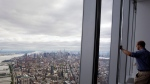 A visitor to One World Observatory looks over Manhattan, May 20, 2015, in New York. The observatory atop the 104-story One World Trade Center opens to the public on May 29. (AP / Mark Lennihan)