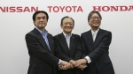 Toyota Motor Corp. executive Kiyotaka Ise, center, Nissan Motor Co. executive Hitoshi Kawaguchi, left, and Honda Motor Co., executive Toshihiro Mibe join hands during a press conference on the collaboration of hydrogen fueling stations in Tokyo on July 1, 2015. (AP / Koji Sasahara)