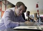 In this photo taken, Wednesday, June 10, 2015, Luis Duran fills out a job application during a job fair in Sunrise, Fla. (AP/Alan Diaz)