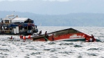 Rescuers help passengers from a capsized ferry boat, right, in Ormoc city on Leyte Island, Philippines, Thursday, July 2, 2015.  (AP / Ignatius Martin)