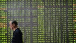 An investor walks by the screen displaying stock prices in a brokerage house in Hangzhou in eastern China's Zhejiang province Friday, June 26, 2015. (Chinatopix)
