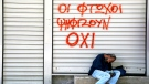 A man sleeps, holding an icon of Jesus Christ, outside a closed shop with spray paint reading 'Poor vote 'NO'' in central Athens, on Saturday, July 4, 2015. (AP / Petros Karadjias)
