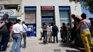 People, right, wait to enter a bank for limited services as others use an ATM of the branch in Athens, Monday, July 6, 2015. (AP / Petr David Josek)