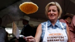 Alberta Premier Rachel Notley flips pancakes at the annual Premier's Stampede breakfast in Calgary, Alta., on Monday, July 6, 2015. (Jeff McIntosh / THE CANADIAN PRESS)