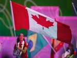 Canada's flag bearer, women's basketball team member Kia Nurse, right, carries the Canadian flag during the closing ceremonies for the Toronto 2015 Pan Am Games in Toronto, Ont., on Sunday July 26, 2015. (Mark Blinch/THE CANADIAN PRESS)