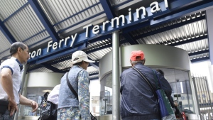 Visitors heading for the Toronto islands line up at the Jack Layton ferry terminal to purchase boarding tickets on June 17 2014. (Fred Lum  / The Globe and Mail)