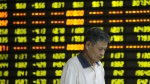 A man walks past stock market quotation on display at a business lobby of a security company in Huaibei, east China's Anhui Province on July 27, 2015. (Xinhua News Agency / Xie Zhengyi)