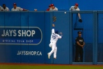 Toronto Blue Jays' Jose Bautista can't catch a fly ball against the Philadelphia Phillies during the fifth inning of MLB interleague baseball action in Toronto, Tuesday July 28, 2015. (Mark Blinch / THE CANADIAN PRESS)