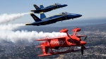 Team Oracle stunt pilot Sean Tucker, bottom, is joined in close formation by a pair of U.S. Navy Blue Angels as they trail vapor during an air show practice run before Seafair Weekend, in Seattle, Thursday, July 30, 2015. (AP / Elaine Thompson)