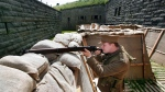 """Stephen Loney, portraying a Lance Corporal with the 25th Battalion, Nova Scotia Rifles,takes aim over some sandbags of a replica First World War trench at the Halifax Citadel on Thursday, July 16, 2015. Parks Canada and the Halifax Citadel National Historic Site will launch the First World War Trench Experience to commemorate the 100th anniversary of the composition of """"In Flanders Fields"""" on July 18-19. THE CANADIAN PRESS/Darren Pittman"""