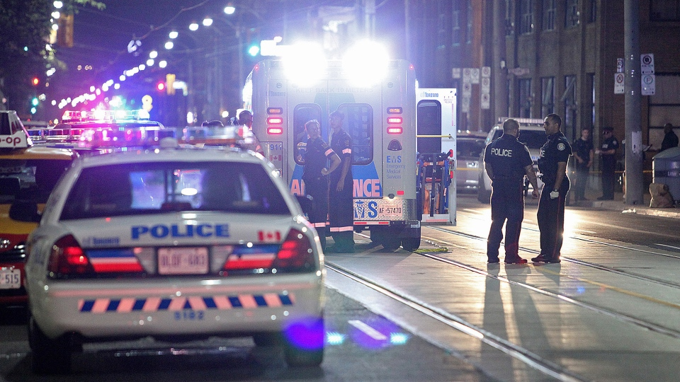 Paramedics and police stand at the scene of a shooting in downtown Toronto early Wednesday, Aug. 19, 2015. (John Hanley / CTV Toronto)
