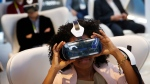 In this Jan. 6, 2015 file photo, Yasmin Moorman looks into the Galaxy Gear VR headset at the Samsung booth during the International CES, in Las Vegas. While more than 1,500 attendees are expected on Saturday, Aug. 29, 2015, at the VRLA expo, the event probably won't feel very crowded. . (AP / John Locher, File)