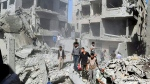 This picture released by the Douma Revolution News Network on their Facebook page, shows Syrians inspecting damage following an airstrike on a Damascus suburb, in this file photo from Saturday, Aug. 22, 2015. (Firas Abdullah/Douma Revolution News Network Facebook page via AP)