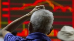 An investor scratches his head near an electronic board displaying market movements at a brokerage in Beijing on Aug. 31, 2015. (AP / Ng Han Guan)