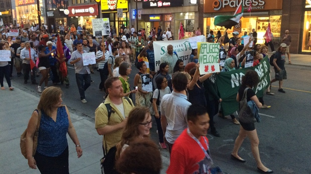 Demonstrators march down Yonge Street on Sept. 4, calling for Canada to accept more migrants. (Tracy Tong/CP24)