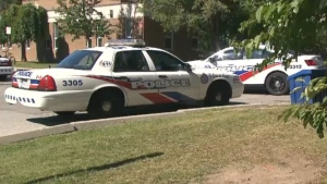 Police vehicles are parked outside George S. Henry Academy in Toronto on Thursday, Sept. 24, 2015.