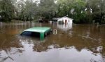 A vehicle and a home are swamped with floodwater from nearby Black Creek in Florence, S.C., Monday, Oct. 5, 2015 as flooding continues throughout the state following several days of rain. (AP Photo/Gerry Broome)
