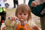Ava Dawson, 3, decorates a small pumpkin with colored markers during the annual Fall Harvest Festival at Ella Sharp Museum in Jackson, Mich., Sunday, Oct. 4, 2015. (Jessica Christian/Jackson Citizen Patriot via AP)