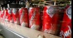 Budweiser cans run through a filling machine at the Anheuser-Busch brewery in the Van Nuys area of Los Angeles is seen Wednesday, March 2, 2011. (AP/Reed Saxon)