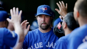 Toronto Blue Jays starting pitcher R.A. Dickey is congratulated by teammates after leaving the game against the Texas Rangers during the fifth inning in Game 4 of baseball's American League Division Series Monday, Oct. 12, 2015, in Arlington, Texas. (AP / LM Otero)