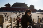 A woman wears a mask as she visits the Forbidden City during a sunny day in Beijing Friday, Dec. 18, 2015. (AP / Ng Han Guan)