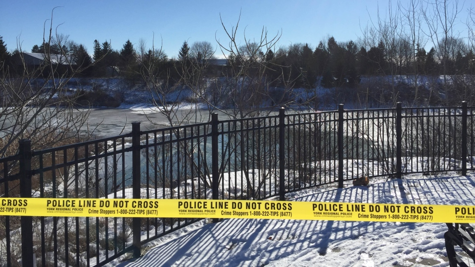 Police tape is seen around a pond where investigators say they have discovered a body. Police have not year confirmed the identity of the body.