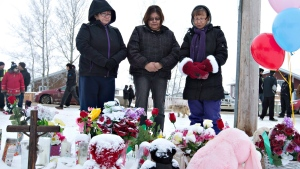 Residents of La Loche, Sask., say a prayer in front of a makeshift memorial at La Loche Community School on Sunday, Jan. 24, 2016. (Jason Franson / THE CANADIAN PRESS)
